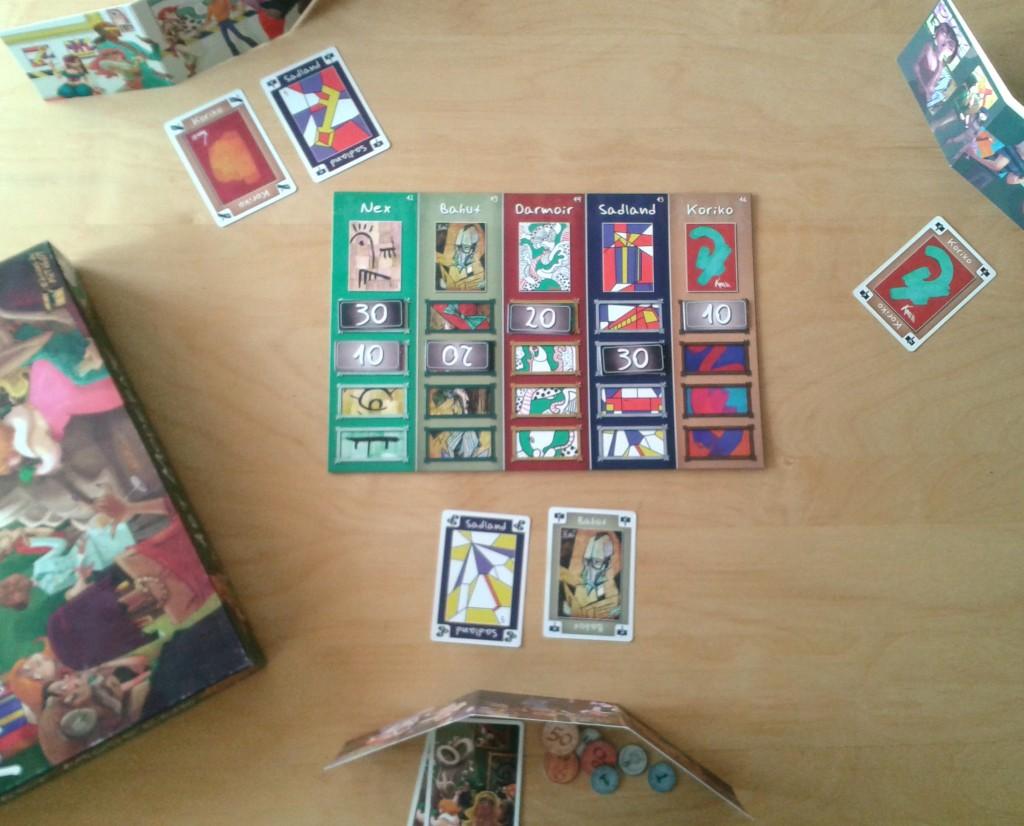 Une partie à trois joueurs. Autour du plateau central, chaque joueur dispose de sa galerie avec les tableaux exposés devant, de sa trésorerie et de sa main de tableaux à vendre.