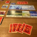 """Une fois le jeu mis en place. """"Lieux"""" placés sur deux rangées de 4 colonnes. La carte """"héros"""" à gauche, le deck en-dessous et la main de départ."""